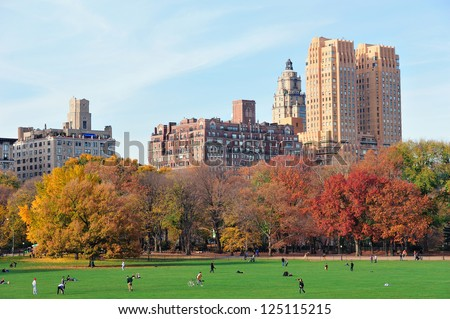 New York City Central Park at autumn in midtown Manhattan with colorful foliage and people on lawn - stock photo