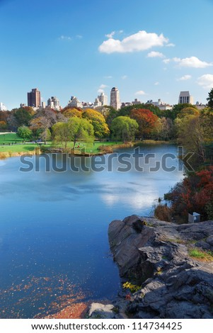 New York City Central Park in Autumn with Manhattan skyscrapers and colorful trees over lake with reflection.