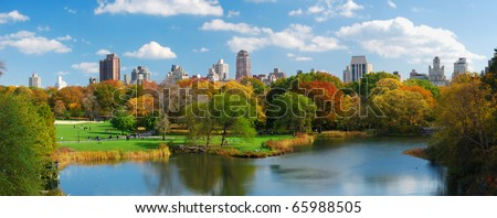 New York City Central Park panorama view in Autumn with Manhattan skyscrapers and colorful trees over lake with reflection.