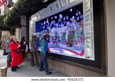 """NEW YORK CITY - DEC. 2:  Spectators view holiday window display in NYC on Dec. 2, 2011.  This year's windows are inspired by a partnership with """"Make A Wish Foundation."""