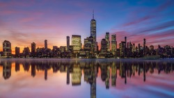 New York City downtown skyline at sunset with beautiful reflection in USA