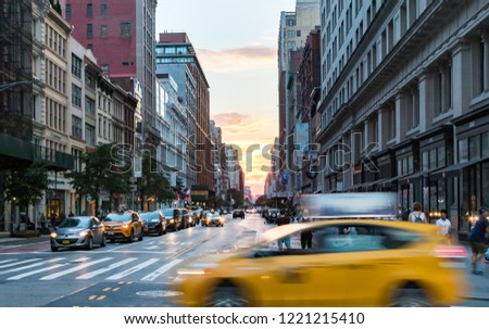 NEW YORK CITY - JULY, 2018: Taxi speeding through the intersection of 23rd Street and 5th Avenue with the colorful light of sunset in the background of the Manhattan skyline. #1221215410