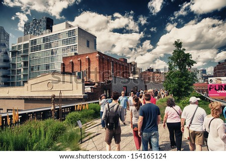 NEW YORK CITY - JUN 15: People walk and relax along the High Line on June 15, 2013. The High Line is a popular linear park built on the elevated train tracks above Tenth Ave in New York City.