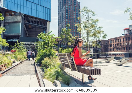 New York City lifestyle woman on mobile phone on urban high line park NYC. Tourist travel vacation girl sitting on bench texting on smartphone app visiting Manhattan touristic attraction.