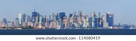 New York City lower Manhattan skyline with Statue of Liberty and urban city skyline over river panorama view.