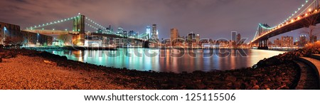 New York City Manhattan Bridge and Brooklyn Bridge with downtown skyline panorama over East River at night - stock photo