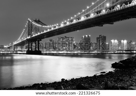 New York City Manhattan Bridge closeup black and white with downtown skyline over East River.