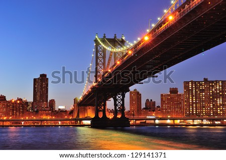 New York City Manhattan Bridge over East River at dusk illuminated with light with reflections and downtown skyline viewed from Brooklyn.