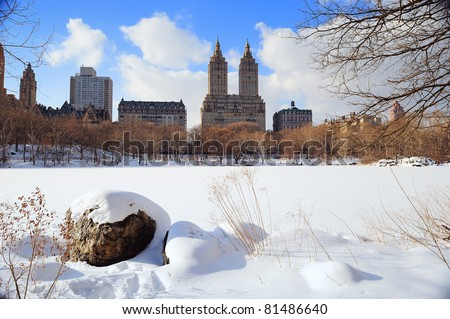 New York City Manhattan Central Park in winter with ice and snow over lake with rocks, skyscrapers and blue cloudy sky at dusk. #81486640