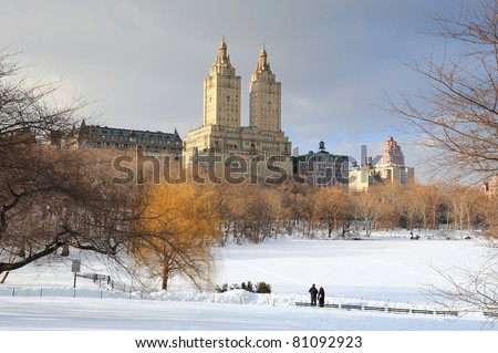 New York City Manhattan Central Park in winter with ice and snow over lake with skyscrapers and blue cloudy sky at dusk. #81092923