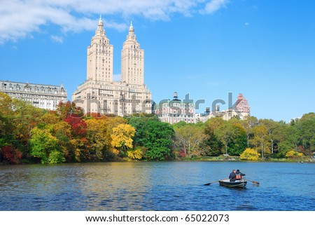 New York City Manhattan Central Park panorama in Autumn lake with skyscrapers and colorful trees over with reflection with boat.