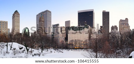New York City Manhattan Central Park panorama in winter with snow, freezing lake and skyscrapers at dusk.