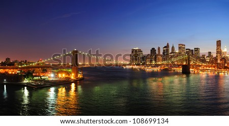 New York City Manhattan downtown skyline aerial view at dusk with skyscrapers lit over East River with reflections.