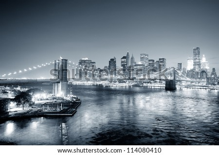 New York City Manhattan downtown skyline aerial view black and white at dusk with skyscrapers lit over East River with reflections. - stock photo