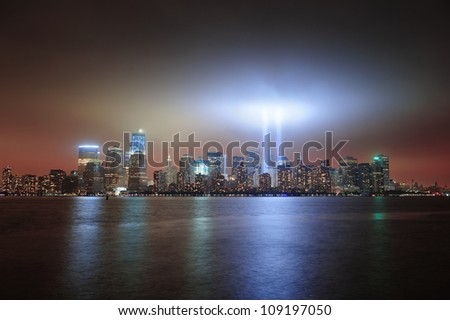 New York City Manhattan downtown skyline at night from Liberty Park with light beams in memory of September 11 viewed from New Jersey waterfront.