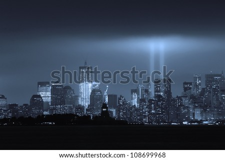 New York City Manhattan downtown skyline black and white at night with statue of liberty and light beams in memory of September 11 viewed from New Jersey waterfront.
