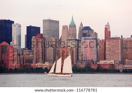 New York City Manhattan downtown skyline with boat at sunset over Hudson River panorama