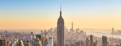 New York City. Manhattan downtown skyline with illuminated Empire State Building and skyscrapers at sunset. Panoramic composition.