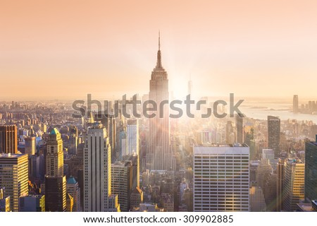 New York City. Manhattan downtown skyline with illuminated Empire State Building and skyscrapers at sunset. Horizontal composition. Warm evening colors. Sunbeams and lens flare.