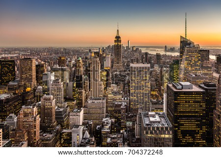 New York City. Manhattan downtown skyline with illuminated Empire State Building and skyscrapers at dusk. #704372248