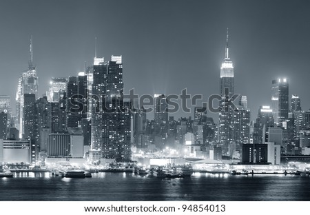 New York City Manhattan midtown skyline black and white at night with skyscrapers lit over Hudson River with reflections.