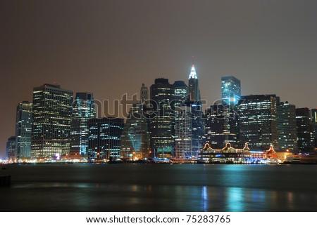 New York City Manhattan night scene panorama with city skyline over Hudson River.