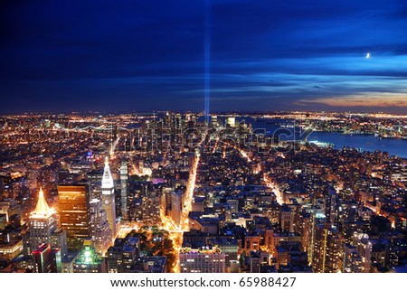 New York City Manhattan panorama view at night with office building skyscrapers skyline illuminated over Hudson River and two light beam in memory of September 11.