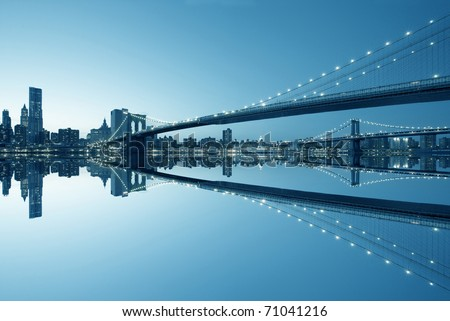 New York City Manhattan skyline and Brooklyn Bridge at dusk with reflection