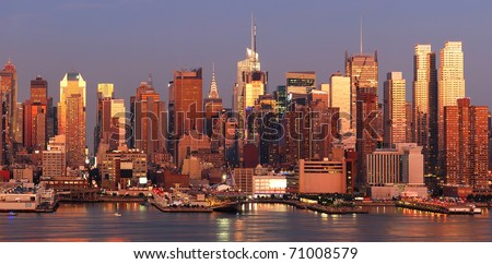 New York City Manhattan skyline panorama at sunset with Times Square and skyscrapers with reflection over Hudson river.