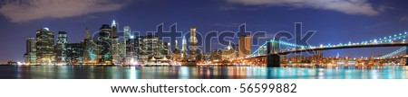 New York City Manhattan skyline panorama with Brooklyn Bridge and office skyscrapers building in at dusk illuminated with lights at night - stock photo