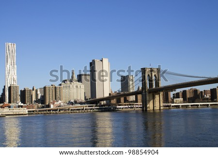 New York City Manhattan skyline with Brooklyn Bridge and skyscrapers over Hudson River in the morning