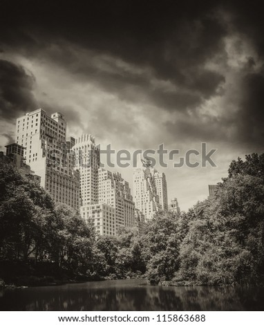 New York City - Manhattan Skyscrapers from Central Park with Trees and Lake.