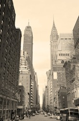 New York City Manhattan street view with Chrysler Building skyscrapers and busy traffic black and white.
