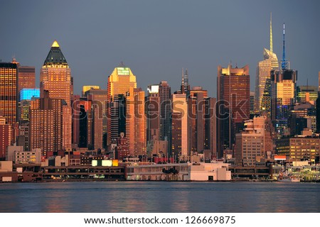 New York City Manhattan sunset panorama with historical skyscrapers over Hudson River with beautiful red color sunshine reflection viewed from New Jersey Weehawken waterfront.