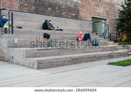 NEW YORK CITY - MAY 2015: People relaxing on the High Line Park. The High Line is a park built on an historic freight rail line elevated above the streets in the West Side.