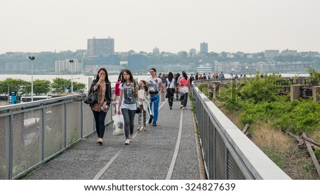 NEW YORK CITY - MAY 16, 2015: People walking on the High Line Park. The High Line is a park built on an historic freight rail line elevated above the streets in the West Side.
