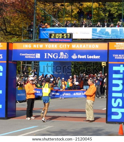 New York City Mayor Michael Bloomberg holds the finish line tape as Marilson Gomes dos Santos of Brazil finishes first in the 2006 ING New York City Marathon