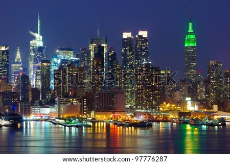 New York City midtown skyline at night over Hudson river