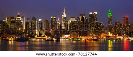 New York City midtown skyline panorama at night over Hudson river, USA