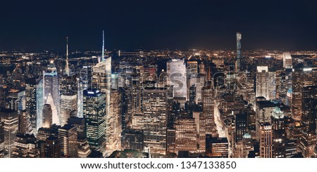 New York City midtown skyline panorama with skyscrapers and urban cityscape at night.