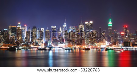 New York City night skyline panorama over Hudson river with boat and skyscraper and colorful reflections.