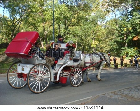 NEW YORK CITY - NOV 10: People enjoy carriage ride in Central Park, November 10, 2011 in New York City. Horse-Drawn Carriages are a wonderful way to experience the beauty of the Park.