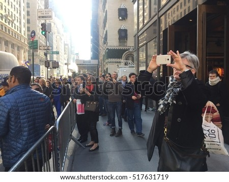 NEW YORK CITY - NOVEMBER 17, 2016: Tourists and pedestrians look and take pictures & selfies in front of Trump Tower. There is heightened security police NYPD   for activists and protestors protests.
