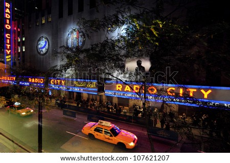 NEW YORK CITY - OCTOBER 15:New York Taxicab passing at night by the Radio City Music Hall on October 15, 2009 in Manhattan New York. Radio City Music Hall was declared as NY city landmark in 1978.