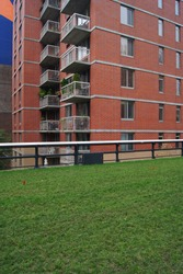 New York city residential view. Red brick tall building with balconies and green lawn in front.
