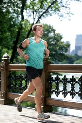 New York City runner running listening to music with smartphone armband. Athletic young man exercising cardio using mobile phone app and earphones for workout in Manhattan's Central Park in summer.