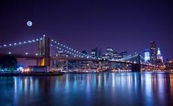 New York City's Brooklyn Bridge and Manhattan skyline illuminated at night with a full moon overhead.