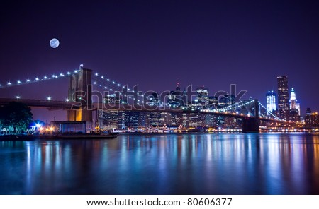 New York City's Brooklyn Bridge and Manhattan skyline illuminated at night with a full moon overhead. #80606377
