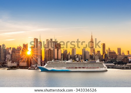 New York City skyline at sunrise, as viewed from Weehawken, along the 42nd street canyon. A large cruise ship sails Hudson river, while sun beams burst between the skyscrapers.