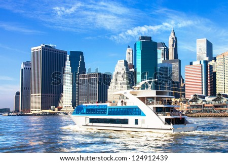 New York City skyline viewed from the water with a harbor boat in the foreground